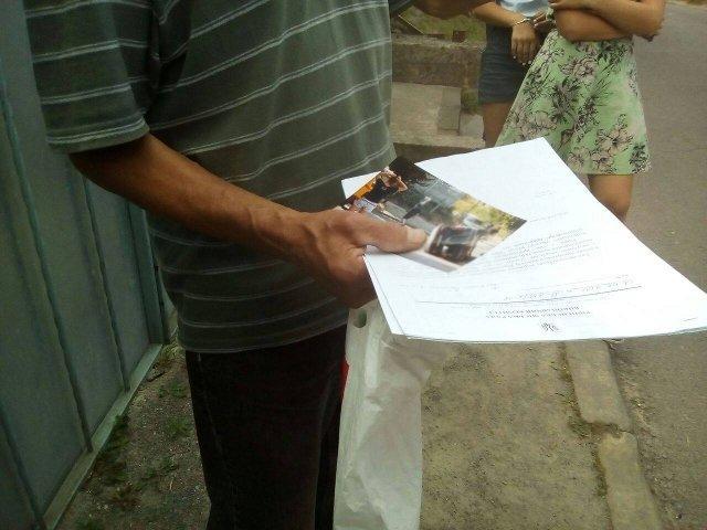Мешканець вулиці Межова тримає документи
